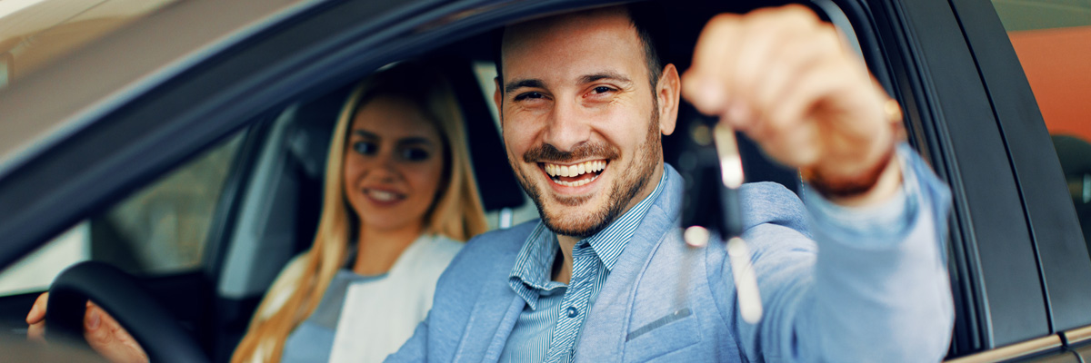 happy couple in their car holding up a pair of keys