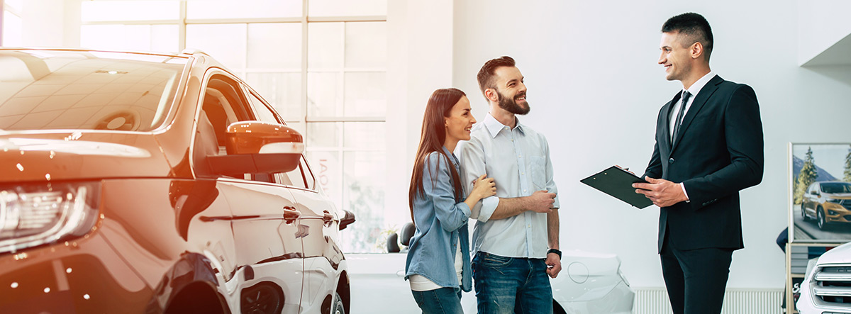Young stylish couple choosing car to buy at dealership