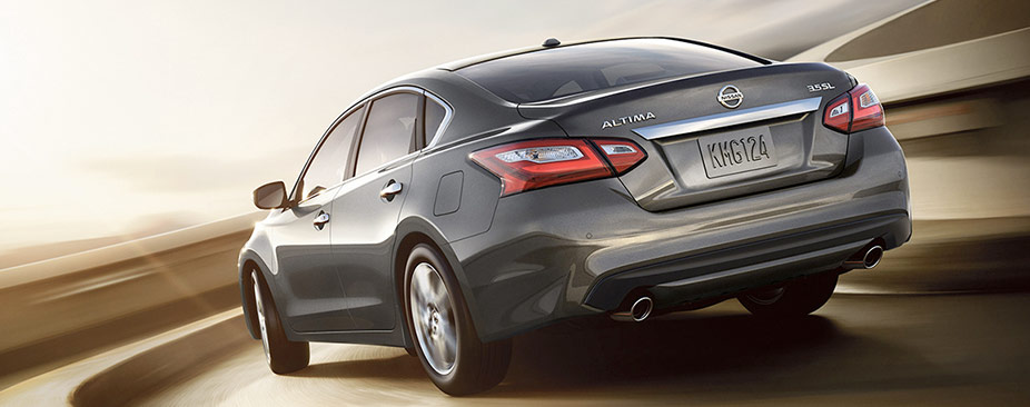 2018 Nissan Altima® sedan, rear view, shown in Gun Metallic driving in desert
