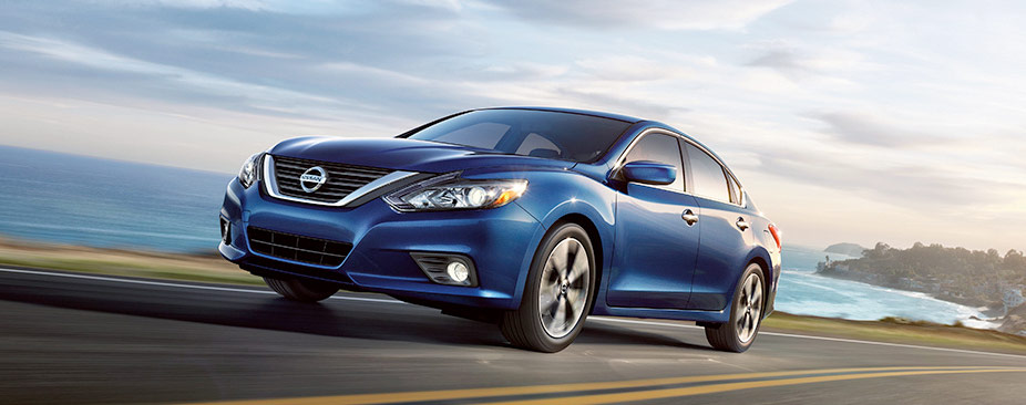 2018 Nissan Altima® sedan, driving on an ocean side highway, shown in Deep Pearl Blue